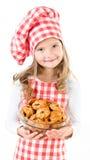 Glimlachend leuk meisje in de holdingskom van de chef-kokhoed met koekjes Stock Foto