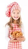 Glimlachend leuk meisje in de holdingskom van de chef-kokhoed met koekjes Royalty-vrije Stock Fotografie