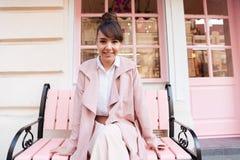 Glimlachend leuk meisje in roze jasjezitting op de bank royalty-vrije stock afbeeldingen