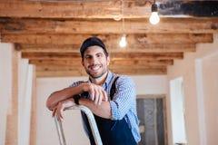 Glimlachend manusje van alles die zich op de ladder bevinden royalty-vrije stock foto's