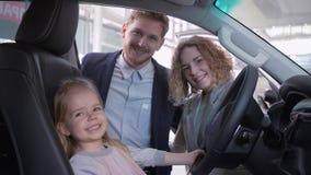 Glimlachend meisje achter wiel van nieuw voertuig samen met mamma en papa terwijl het kopen van familieauto bij het handel drijve stock video