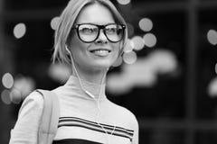 Glimlachend meisje amid de zwarte witte foto van de glasdeur Stock Foto