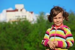 Glimlachend meisje bij gebied tegen het huis stock afbeelding
