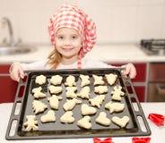 Glimlachend meisje in chef-kokhoed met bakselblad van koekjes Stock Foto's