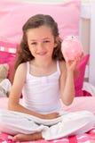 Glimlachend meisje dat een piggy-bank houdt Stock Afbeelding