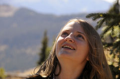 Glimlachend meisje dat omhoog op bergtop kijkt Royalty-vrije Stock Foto