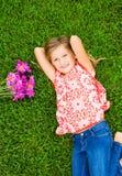 Glimlachend meisje dat op groen gras met bloemen ligt Royalty-vrije Stock Foto's
