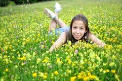 Glimlachend meisje dat op het groene gras en de bloem rust royalty-vrije stock afbeeldingen