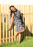 Glimlachend meisje dat op omheining leunt Royalty-vrije Stock Foto's