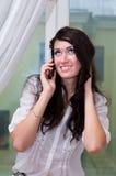Glimlachend meisje dat op telefoon thuis spreekt Stock Foto's