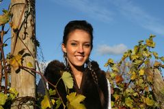 Glimlachend meisje dat zich in een wijngaard bevindt stock foto