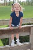 Glimlachend meisje dat zich op de omheining bevindt Royalty-vrije Stock Foto's