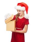 Glimlachend meisje in de hoed van de santahelper met giftdoos Royalty-vrije Stock Afbeelding