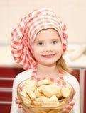 Glimlachend meisje in de holdingskom van de chef-kokhoed Royalty-vrije Stock Foto