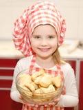 Glimlachend meisje in de holdingskom van de chef-kokhoed met koekjes Royalty-vrije Stock Afbeelding
