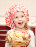 Glimlachend meisje in de holdingskom van de chef-kokhoed met koekjes Royalty-vrije Stock Fotografie