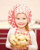 Glimlachend meisje in de holdingskom van de chef-kokhoed met koekjes Stock Afbeeldingen