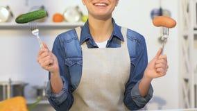 Glimlachend meisje in de vorken van de schortholding met worst en komkommer in handen, keus stock videobeelden