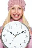 Glimlachend meisje in de winterkleren die klok tonen Stock Foto's