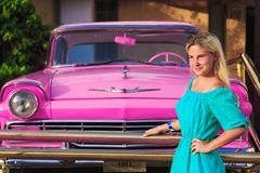 Glimlachend meisje dichtbij roze retro auto royalty-vrije stock afbeeldingen