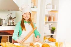 Glimlachend meisje die bakkerijdeeg maken bij de keuken Stock Foto's