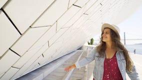 Glimlachend meisje die dichtbij de moderne bouw op dijk lopen stock footage
