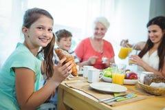 Glimlachend meisje die een croissant eten terwijl het hebben van ontbijt stock fotografie