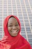 Glimlachend meisje die een rode headscarf in de straat dragen, dertien jaar oud Royalty-vrije Stock Fotografie