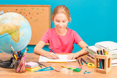 Glimlachend meisje die haar thuiswerk doen Royalty-vrije Stock Afbeelding