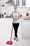 Glimlachend meisje die het huis schoonmaken stock foto