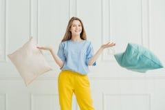 Glimlachend meisje die hoofdkussens werpen Gelukkige speelse vrouw in pyjama Royalty-vrije Stock Foto's