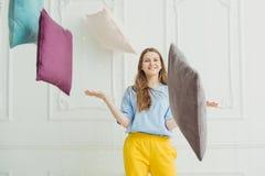 Glimlachend meisje die hoofdkussens werpen Gelukkige speelse vrouw in pyjama Stock Foto
