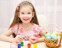 Glimlachend meisje die kleurrijke paaseieren schilderen Stock Afbeelding