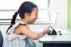 Glimlachend meisje die laptop in klaslokaal met behulp van royalty-vrije stock foto's