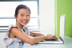 Glimlachend meisje die laptop met behulp van bij lijst in klaslokaal stock afbeeldingen