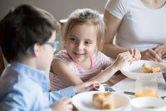 Glimlachend meisje die met broer bij ontbijt thuis spreken royalty-vrije stock foto