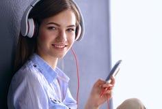 Glimlachend meisje die met hoofdtelefoons op de vloer dichtbij muur zitten Royalty-vrije Stock Afbeeldingen