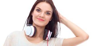 Glimlachend meisje die met hoofdtelefoons op de vloer dichtbij muur zitten Royalty-vrije Stock Fotografie