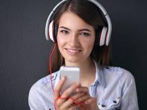 Glimlachend meisje die met hoofdtelefoons op de vloer dichtbij muur zitten Stock Fotografie