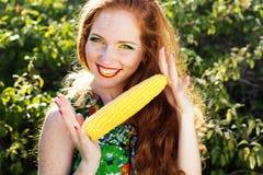 Glimlachend meisje die met sproeten maïskolf houden stock foto