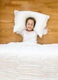 Glimlachend meisje die op vloer in pyjama's liggen royalty-vrije stock afbeeldingen