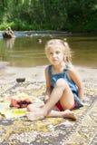 Glimlachend meisje die picknick op de rivieroever hebben Stock Foto's