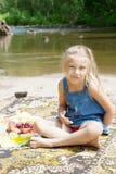 Glimlachend meisje die picknick op de rivieroever hebben Royalty-vrije Stock Foto