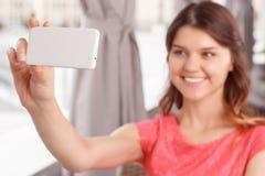 Glimlachend meisje die selfie in koffie doen stock fotografie