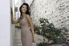 Glimlachend meisje die zich dichtbij de oude steenmuur bevinden Mooie vrouw met lang haar dat sexy buitenkant in vakantie in Grie royalty-vrije stock foto's