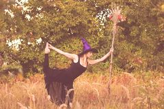 Glimlachend meisje in heksenkostuum die geschiktheid doen Royalty-vrije Stock Fotografie