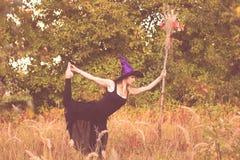 Glimlachend meisje in heksenkostuum die geschiktheid doen Stock Afbeelding