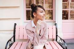 Glimlachend meisje in het roze laag ontspannen op de bank in openlucht Stock Afbeelding