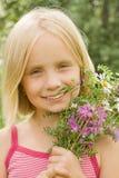 Glimlachend meisje met bloemen stock foto's