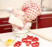 Glimlachend meisje met chef-kokhoed gezette bloem voor bakselkoekjes Royalty-vrije Stock Afbeelding